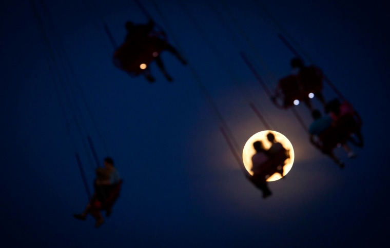 Image: People ride the Luna Park Swing Ride as the Super Moon rises on Coney Island