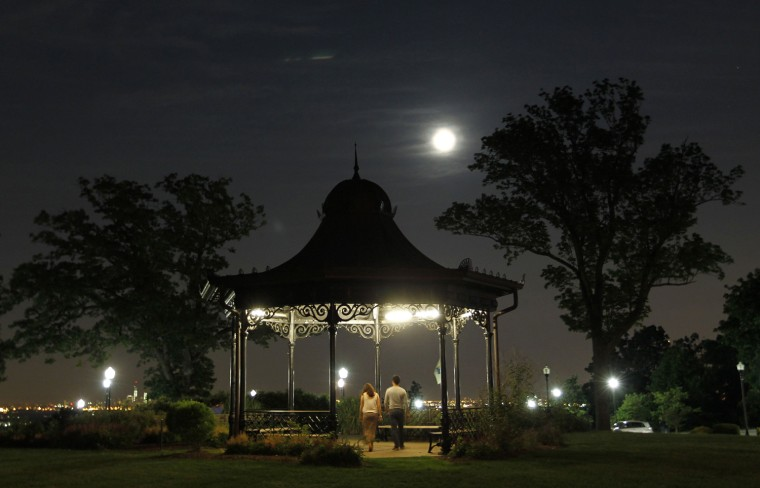 Image: People walk through a gazebo as a super moon rises in West Orange, New Jersey