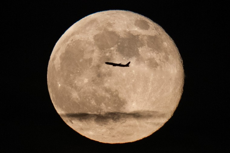 Image: A silhouetted airplane flies past a 'supe rmoon' over New York
