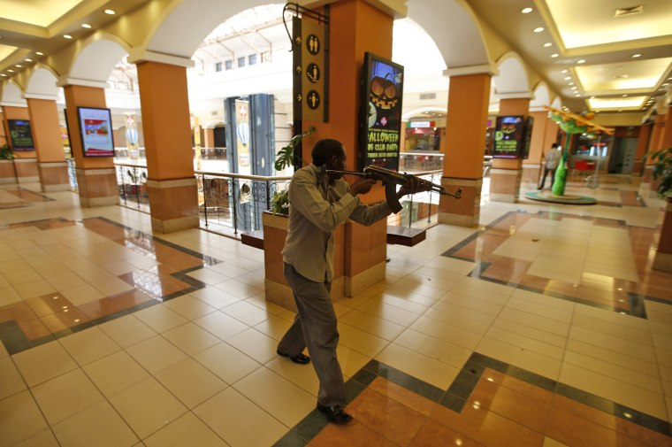 Image: An armed police searches through a shopping centre for gunmen in Nairobi