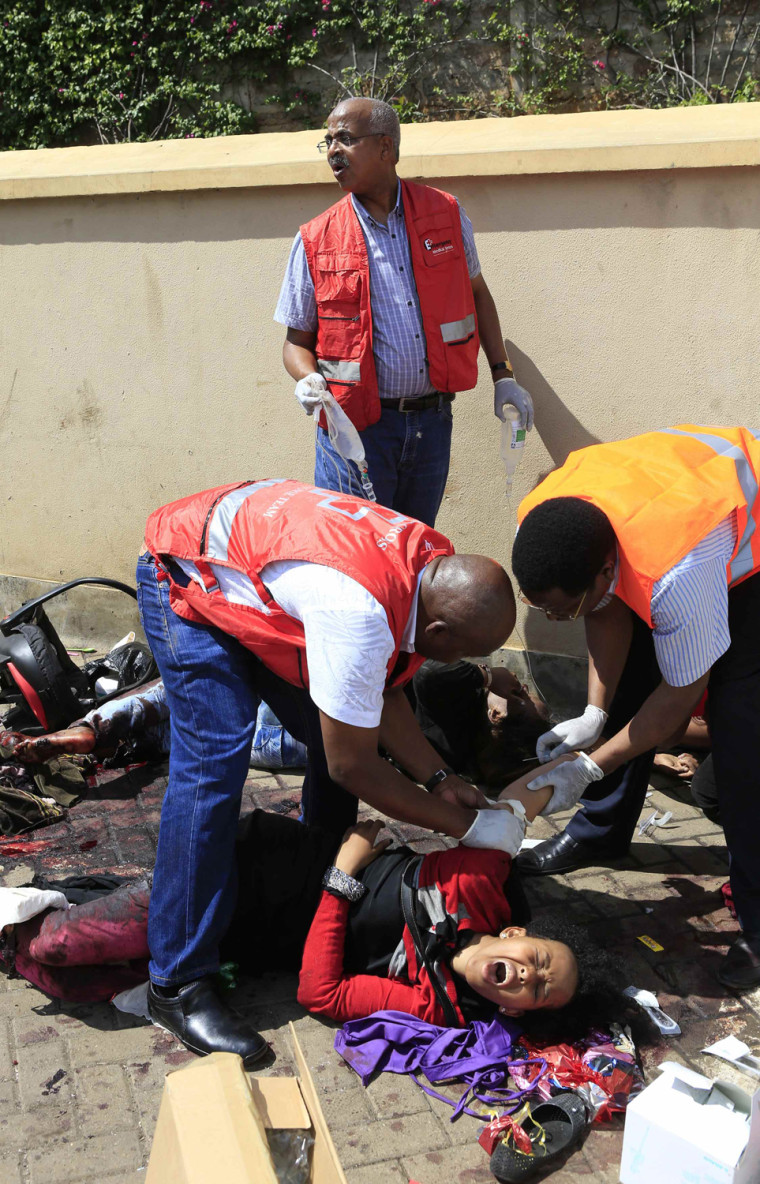 Image: Paramedics help an injured victim after a shooting spree at Westgate shopping centre in Nairobi