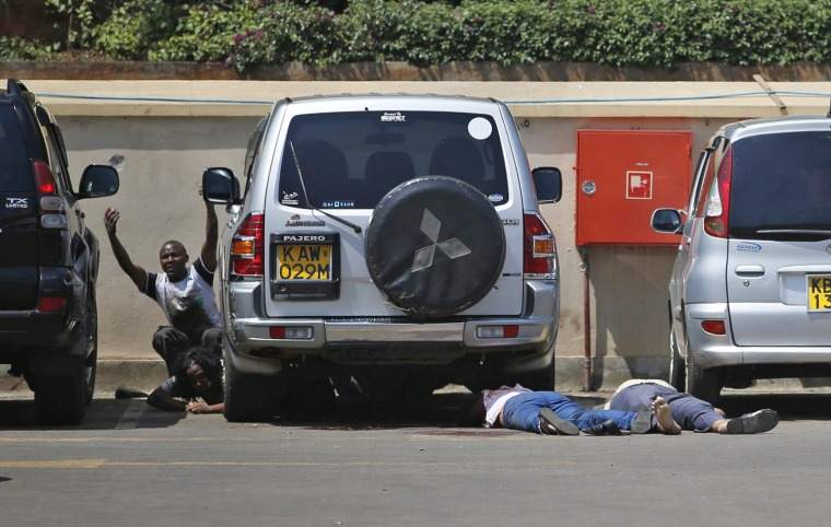 Image: People come out from hiding under a car next to bodies as police search for gunmen in a shopping centre in Nairobi