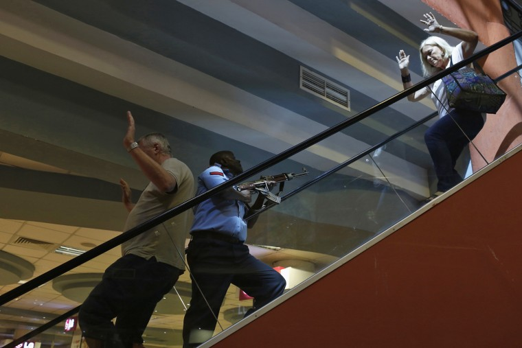 Image: A police officer secures an area as civilians flee inside Westgate Shopping Centre in Nairobi