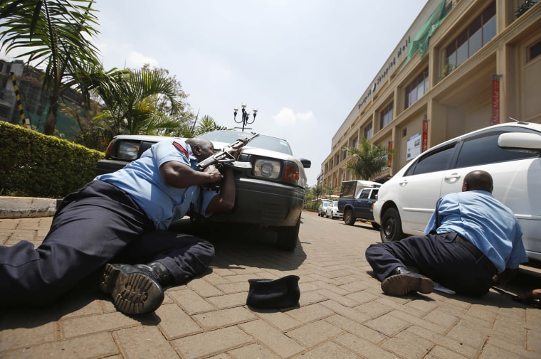 Image: Police take cover outside Westgate shopping centre where gunmen went on a shooting spree in Nairobi