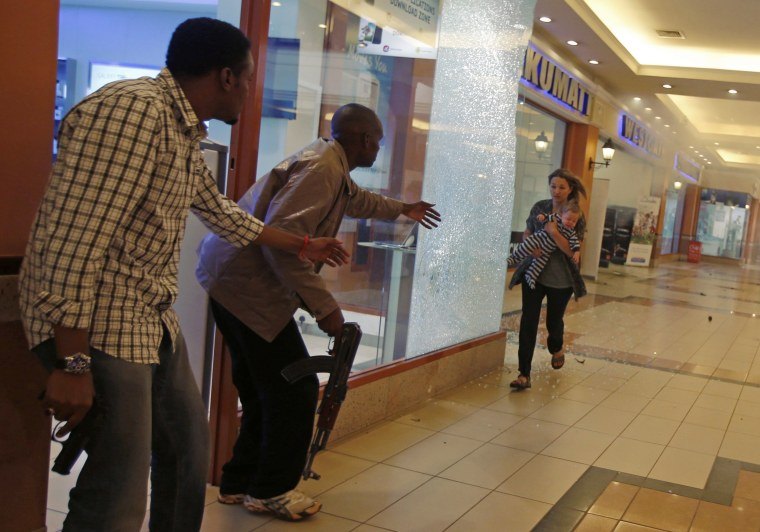 Image: Armed police guide a woman carrying a child to safety as they hunt gunmen who went on a shooting spree at Westgate shopping centre in Nairobi