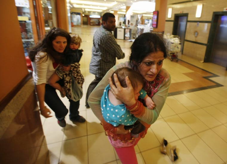 Image: Women carrying children run for safety as armed police hunt gunmen who went on a shooting spree in Westgate shopping centre in Nairobi