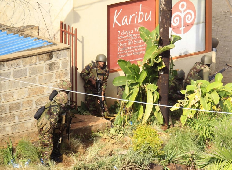Image: Kenya Defence Forces soldiers take cover behind walls near the Westgate shopping centre after an exchange of gunfire inside the mall in Nairobi