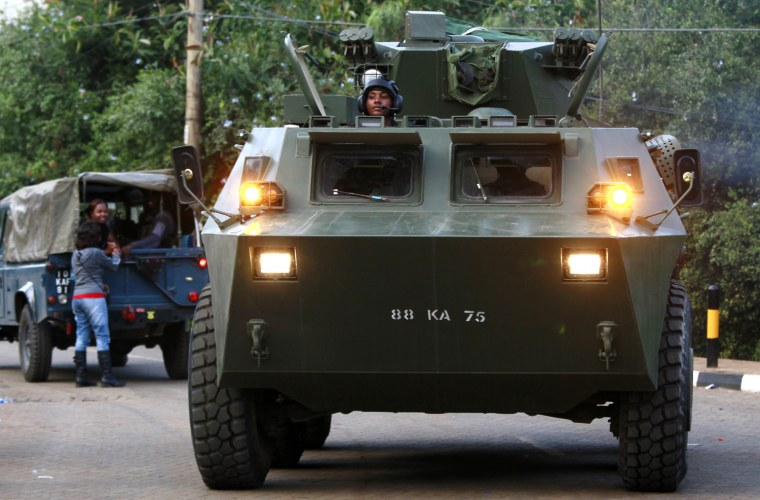 Image: A KDF armoured military vehicle drives from the Westgate shopping centre after an exchange of gunfire inside the mall in Nairobi