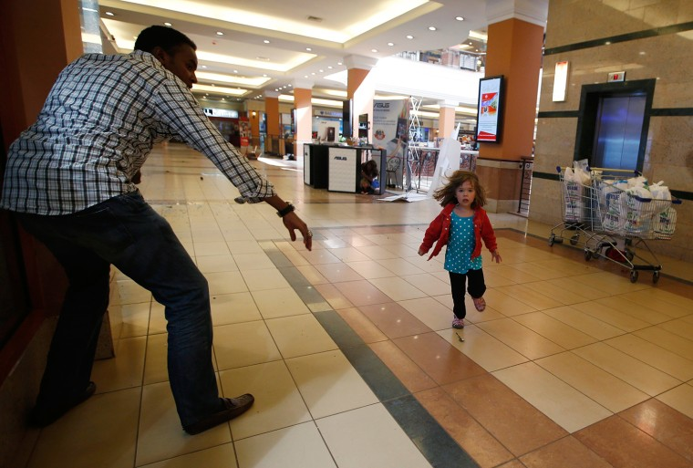 Image: A child runs to safety as armed police hunt gunmen who went on a shooting spree at Westgate shopping centre in Nairobi