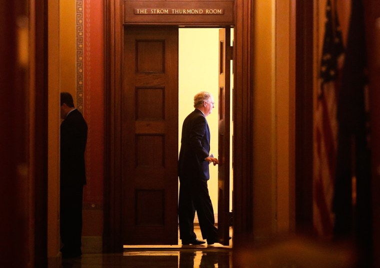 Image: Mitch McConnell of Kentucky closes the door as he meets with Senate Republicans regarding the government shutdown on Oct. 13.