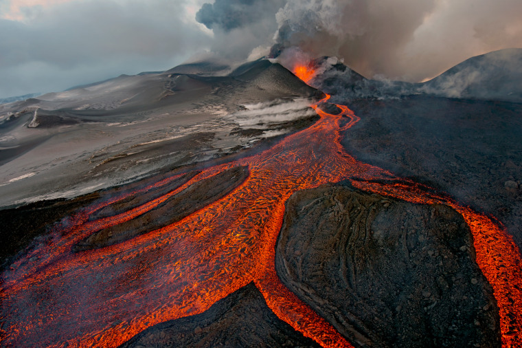 "The cauldron, Sergey Gorshkov (Russia) Winner: Wildscapes On Nov. 29, 2012, Sergey received the call that he had long hoped for. Plosky Tolbachik--one of two vocanoes in the Tolbachik volcanic plateau in central Kamchatka, Russia--had begun to erupt. ""I've gone to the area many times, but it had been 36 years since the last eruption,"" he says. ""so I dropped everything and went."" The only way to approach it was by helicopter, but extreme cold (-40 degrees Fahrenheit) meant Sergey had to wait until it was warm enough for the helicopter to take off. Flying towards the volcano, the cloud of ash, smoke and steam was so thick that he couldn't see the crater. But every so often, a strong wind blew the clouds away, and he could see a 700-foot-high fountain of lava spouting out of the crater and fast-flowing, molten rivers of lava running down it (some of these would travel 6 miles, sweeping away everything in their path.) As gusts of hot air buffeted the helicopter, Sergey worked fast,  strapped to the open door. ""I just kept shooting, kept changing lenses and camera angles, knowing I had this one chance, hoping that I'd take one image that might do justice to what I was witnessing."" That was indeed his last chance. At 1:00 a.m. a new explosion happened, the ground rumbled, huge lava bombs threatened the campsite, and a heavy rain of ash and smoke made it impossible to take pictures. Says Sergey,""I have been to many places and I have seen many extraordinary things, but witnessing the Plosky Tobachik eruption deeply impressed me."""