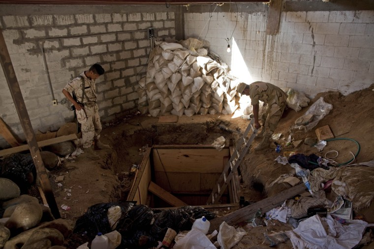 Mexican Army soldiers custody the entrance of a clandestine tunnel connecting warehouses on either side of California's border with Mexico in Tijuana, Thursday, Nov. 4, 2010. Federal authorities in San Diego made one of the largest marijuana seizures in the United States, confiscating more than 20 tons of pot that was smuggled to the country through the underground tunnel that had lighting, ventilation and a rail system to send loads of illegal drugs into California. Mexican authorities also seized more than four tons of drug from the warehouse on their side. (AP Photo/Guillermo Arias)