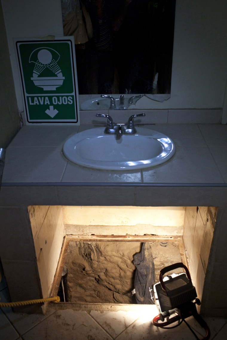 The entrance to a cross border illegal tunnel is lit by a lamp after it was found underneath a bathroom sink by the Mexican army inside a warehouse in Tijuana, Mexico, Thursday July 12, 2012. The 220-yard  tunnel, presumably designed to smuggle drugs into the United States, was incomplete and had not yet crossed the border into San Diego. (AP Photo/Alejandro Cossio)