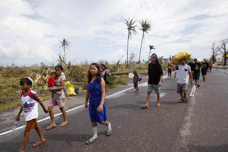 Image: Survivors walk past a damaged town after strong winds brought by super Typhoon Haiyan battered Tacloban city