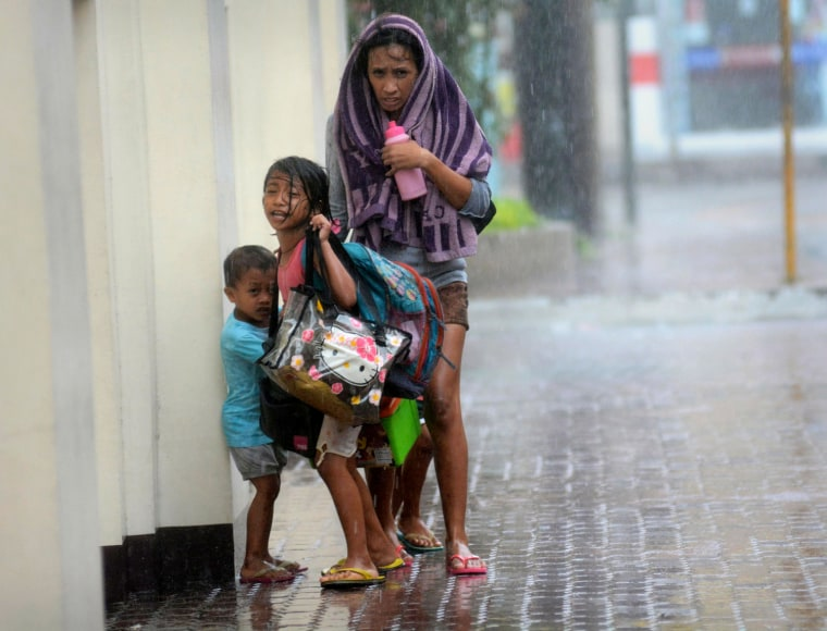 Image: A mother takes refuge with her children as Typhoon Haiyan hits Cebu city