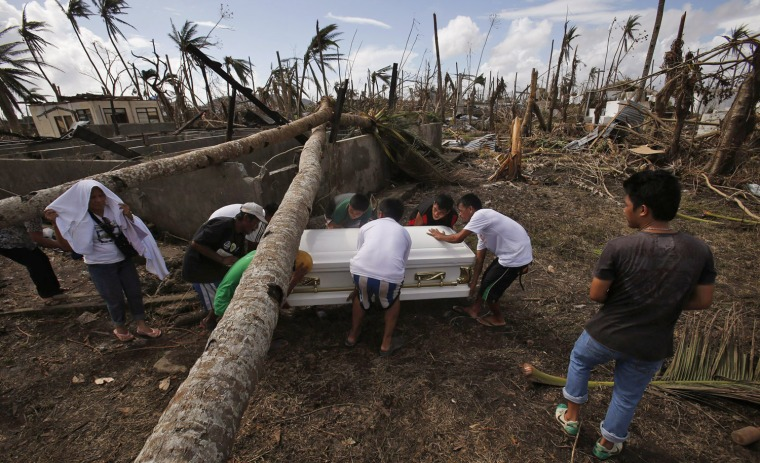 Image: Residents carry a coffin containing the body of a victim of Typhoon Haiyan during a funeral in Tanauan