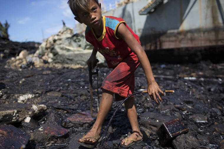 Image: Image: Boy collects scrap iron in Estancia, Philippines