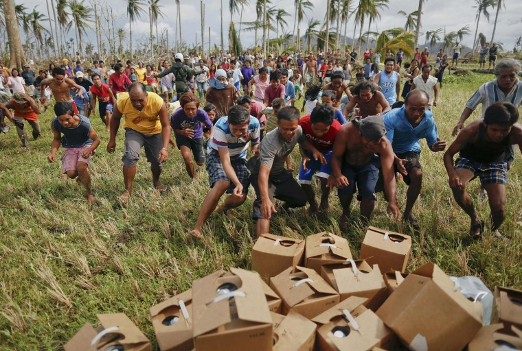 Image: Survivors of Typhoon Haiyan rush to grab fresh water delivered by a U.S. military helicopter to their isolated village north of Tacloban