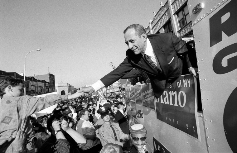 Image: From a campaign bus, Gov. Mario Cuomo of New York shakes hands with supporters.
