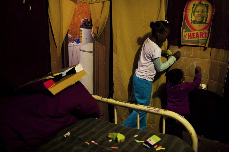 Sharon Harris' children entertain themselves on an improvised chalkboard made out of cardboard in their bedroom in the Baptist Town neighborhood of Greenwood, Mississippi on November 30, 2011.