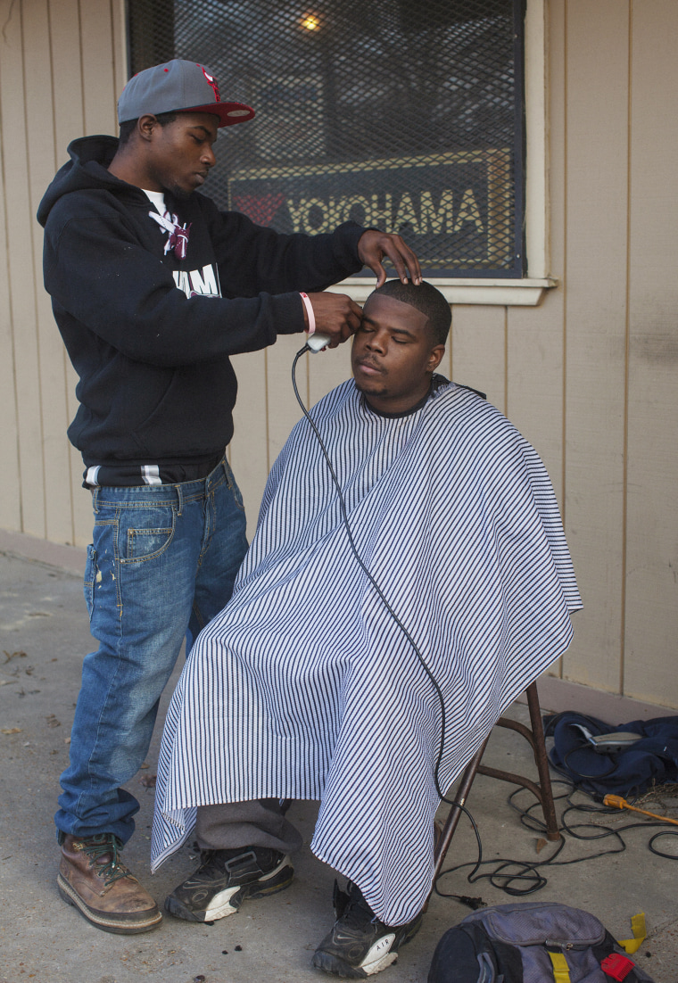 """Lorenzo Gore, 20, gives a trim to Thaddeus Walls, 23, outside of Thaddeus's father's shop in Greenwood, Mississippi on January 31, 2014. As I wrote down their names, the dad chimed in to say, """"And write down that they're both unemployed and looking for jobs!"""""""
