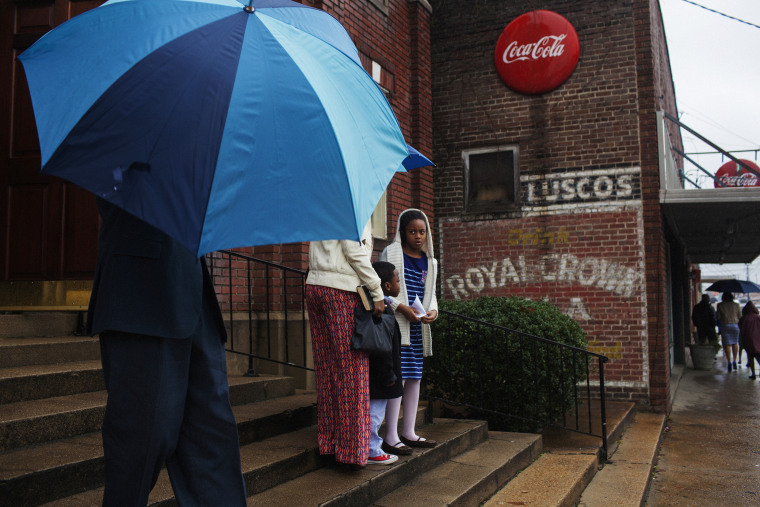 Parishioners step into the rain outside of New Zion Missionary Baptist Church in Greenwood, Mississippi on Super Bowl Sunday, February 2, 2014.