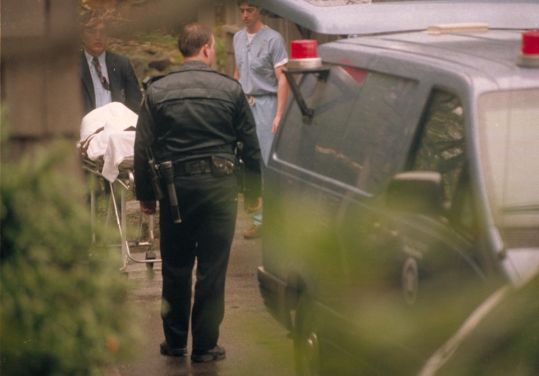 The body of Nirvana lead singer Kurt Cobain is taken to a medical examiner's van, after he was found dead earlier that day at his home in Seattle, Wash., on April 8, 1994. According to a police source, Cobain died from a self-inflicted shotgun wound, and a suicide note was found next to the body. (AP Photo/Robert Sorbo)