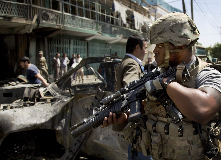 Image: A U.S. soldier arrives to the scene where a suicide car bomber attacked a NATO convoy in Kabul, Afghanistan.