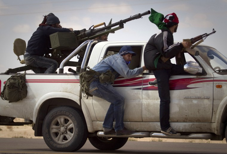 Image: Libyan rebels retreat as mortars from Moammar Gadhafi's forces are fired on them on the frontline of the outskirts of the city of Ajdabiya, south of Benghazi, eastern Libya, Tuesday, March 22.