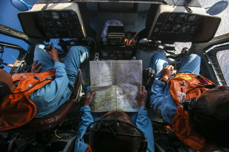 Image: Military personnel work within the cockpit of a helicopter belonging to the Vietnamese airforce during a search and rescue mission off Vietnam's Tho Chu island