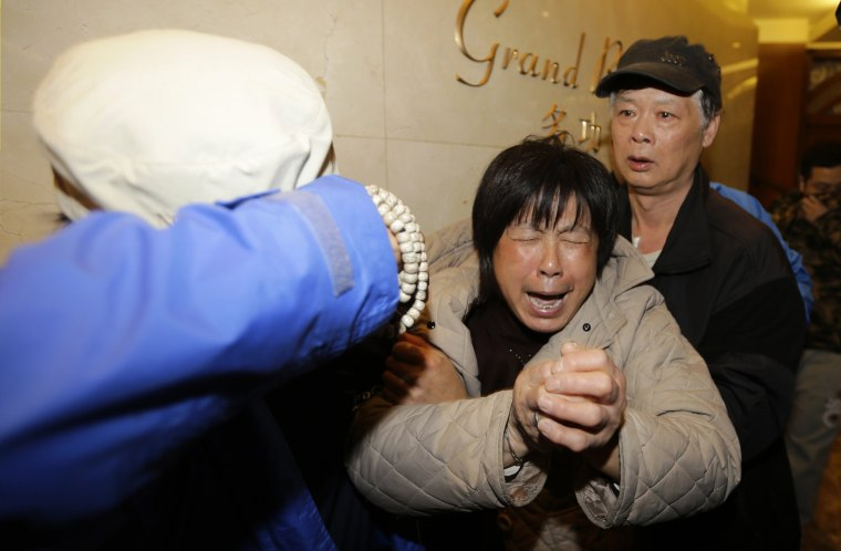 Image: A family member of a passenger aboard Malaysia Airlines flight MH370 cries after watching a television broadcast of a news conference, at the Lido hotel in Beijing