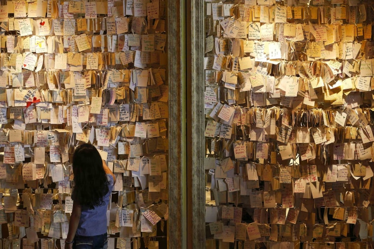 Image: A girl reads some of the messages of hope and support for the passengers of the missing Malaysia Airlines MH370 at a mall outside Kuala Lumpur