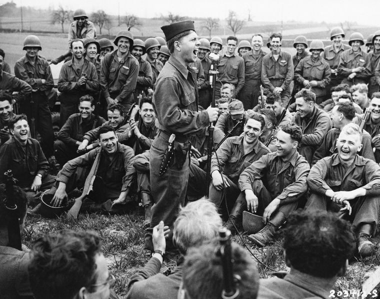 Pfc. Mickey Rooney, former film star, imitates some Hollywood actors for the entertainment of infantrymen of the 44th Division of the U.S. Seventh Army, April 24, 1945. Rooney is a member of a three-man unit making a jeep tour to entertain troops in Germany. (AP Photo)