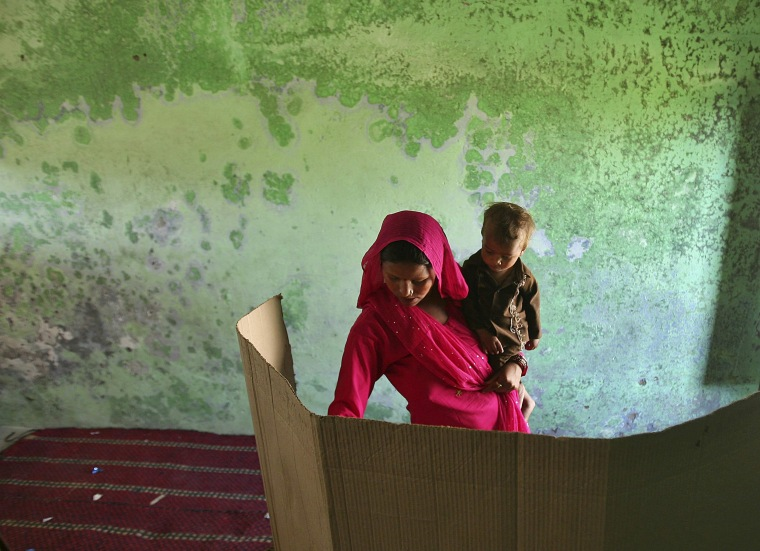 Image: A woman holding her child votes inside a polling station on the outskirts of Jammu