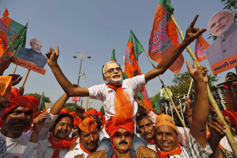 Image: A supporter wearing a mask of Modi, prime ministerial candidate for India's main opposition BJP, cheer as Modi arrives to file nomination papers for the general elections in Vadodara