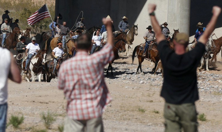 Image: Protesters cheer on horseback riders as they herd cattle that belongs to rancher Cliven Bundy after they were released near Bunkerville