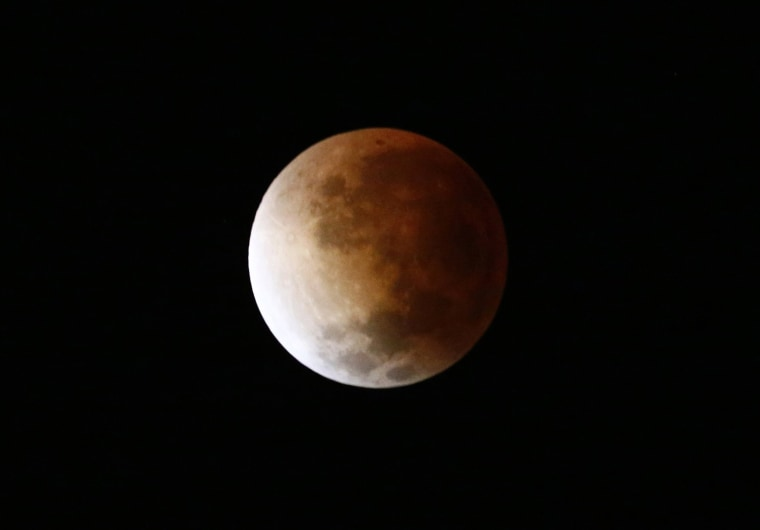 Image: The moon is seen as it begins a total lunar eclipse over Buenos Aires
