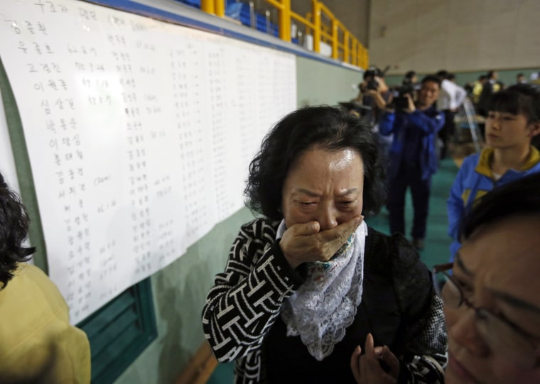 Image: The mother of a passenger who was on a sinking ferry reacts after finding her son's name in the survivors list in Jindo