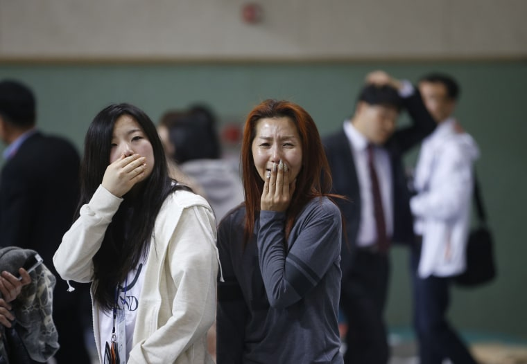 Image: The mother of a passenger who was on a sinking ferry reacts as she finds her son at a gym where rescued passengers gather in Jindo