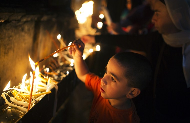 Image: A Christian boy lights a candle inside the Church of the Holy Sepulchre before the Easter Sunday mass procession in Jerusalem's old city