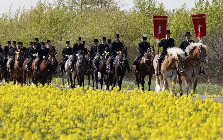 Image: Sorb men of the German Slavic minority, dressed in traditional clothes, ride horses during a ceremonial parade near the village of Wittichenau