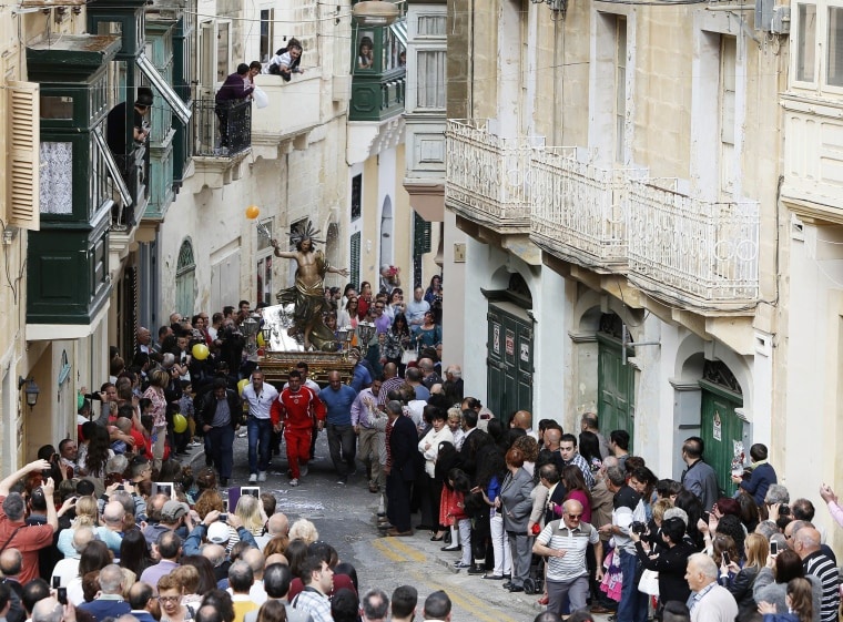 Image: Worshippers run while carrying a statue of the Risen Christ during an Easter Sunday procession in Cospicua