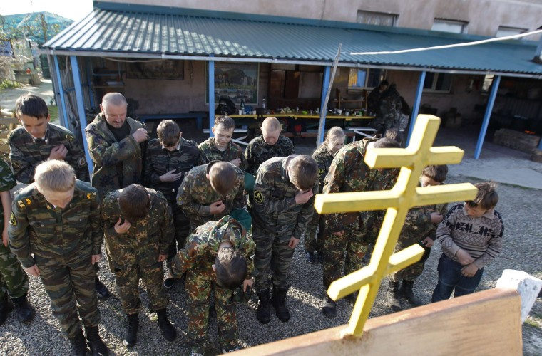 Image: Students from the General Yermolov Cadet School cross themselves in front of an Orthodox crucifix during a two-day field exercise near the village of Sengileyevskoye