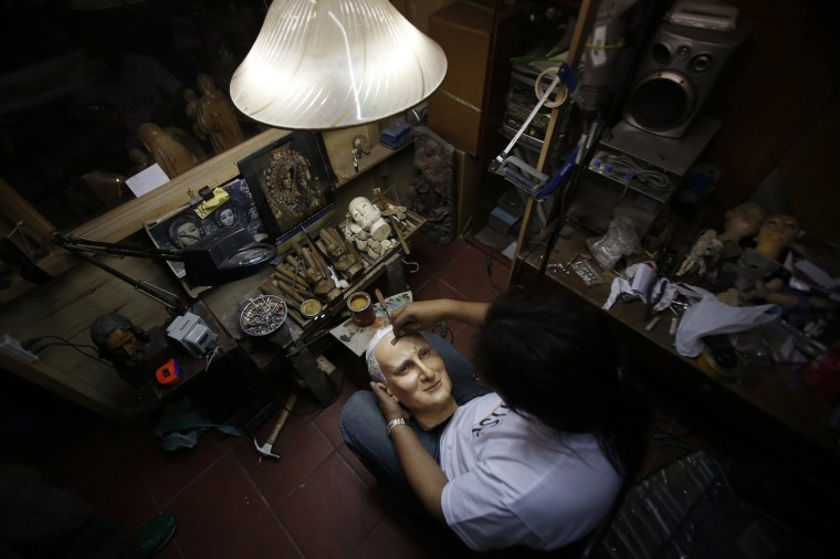 Image: Sculptor Dondon Awa cleans the head of a statue of the late Pope John Paul II at his workshop in Tayuman, metro Manila