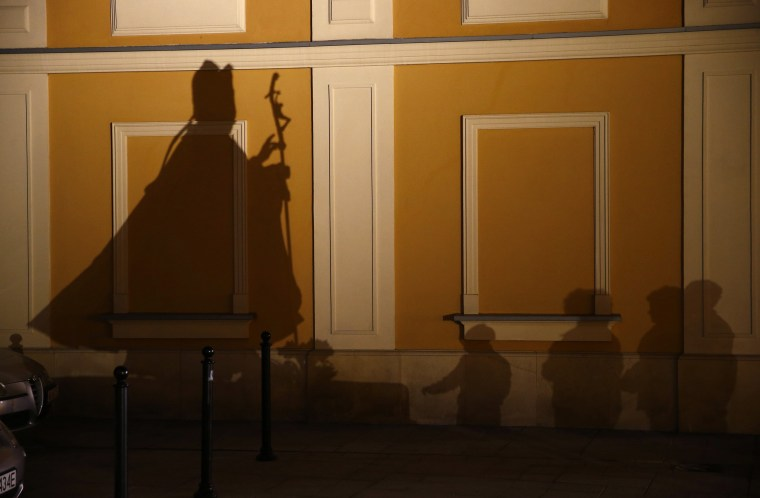 Image: File photo of people casting shadows as they pray in front of a statue of the late Pope John Paul II on the ninth anniversary of his death in Wadowice