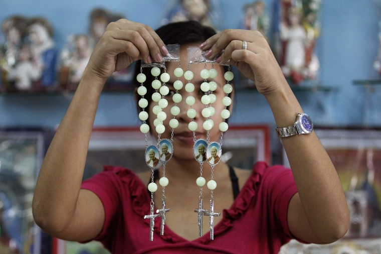 Image: A shop worker poses as she holds up rosaries bearing pictures of Pope John Paul II inside a religious store in Caloocan city, metro Manila