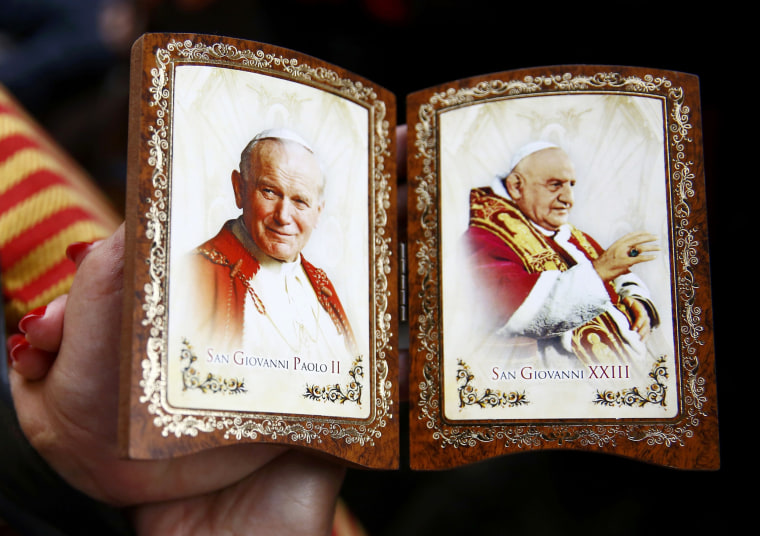 Image: Polish pilgrim displays a souvenir of canonised Popes John Paul II and John XXIII while waiting for mass before the canonisation ceremony in St Peter's Square at the Vatican