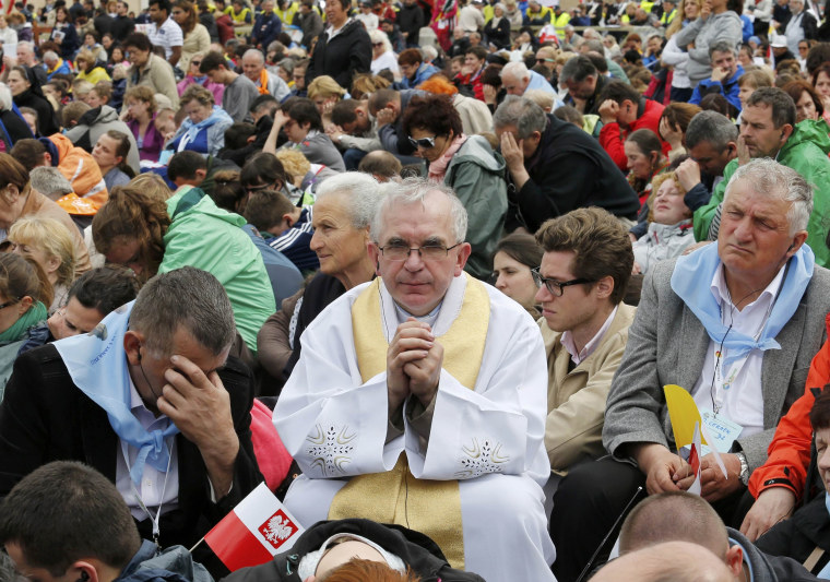 Image: The faithful pray during mass during the canonisation ceremony in St Peter's Square at the Vatican
