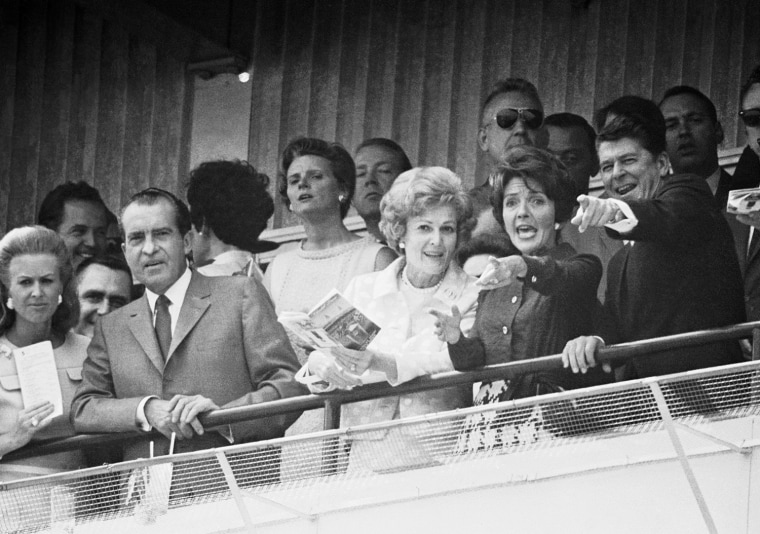 Like typical race fans, Gov. Ronald Reagan and his wife Nancy excitedly follow the progress of a horse running in the sixth race of the Kentucky Derby program in Louisville, Ky., on May 3, 1969.    President Richard Nixon and wife, Pat, are alongside the Reagans in first row of box. (AP Photo)