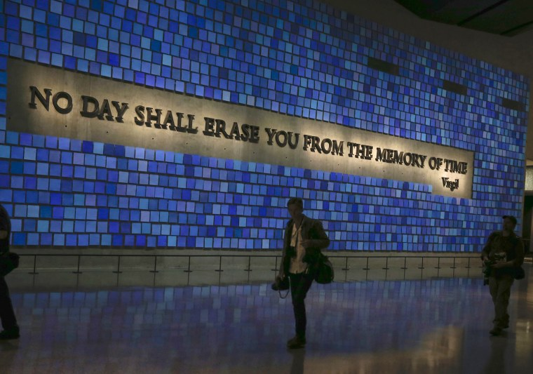 Image: A wall with a quote from Virgil and featuring 2,983 panels for each victim is seen in the National September 11 Memorial & Museum during a media preview in New York